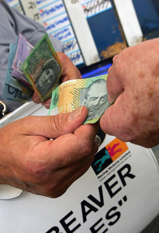 Money changes hands by bookmakers at a race, November, 2005