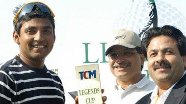 Ajay Jadeja receives a trophy from Rajiv Shukla at a golf tournament