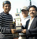 Ajay Jadeja receives a trophy from Rajiv Shukla at a golf tournament