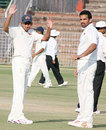 Ajit Agarkar and Zaheer Khan await the resumption of Punjab's second innings