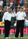 Umpires Steve Davis and Tony Hill look worriedly up into the heavens