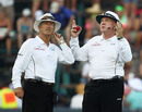 Umpires Steve Davis and Tony Hill look at the overcast sky
