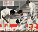 Rahul Dravid is in serious pain after being hit, as the bowler Shahadat Hossain and keeper Mushfiqur Rahim look on
