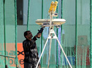 An Indian security official checks a bowling machine in the nets prior to a training session, Jaipur, February 20, 2010