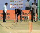Indian security personnel and a sniffer dog check the nets prior to a training session, Jaipur, February 20, 2010