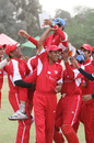 The Hong Kong players hoist coach Tabarak Dar in the air after beating Malaysia by 7 runs