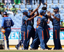 The Indian fielders celebrate the dismissal of Karim Sadiq
