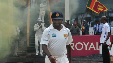 Muttiah Muralitharan walks down a red carpet into the field for his last day of Test cricket