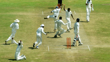 The Sri Lankan fielders converge on Muttiah Muralitharan after he picked his 800th Test wicket