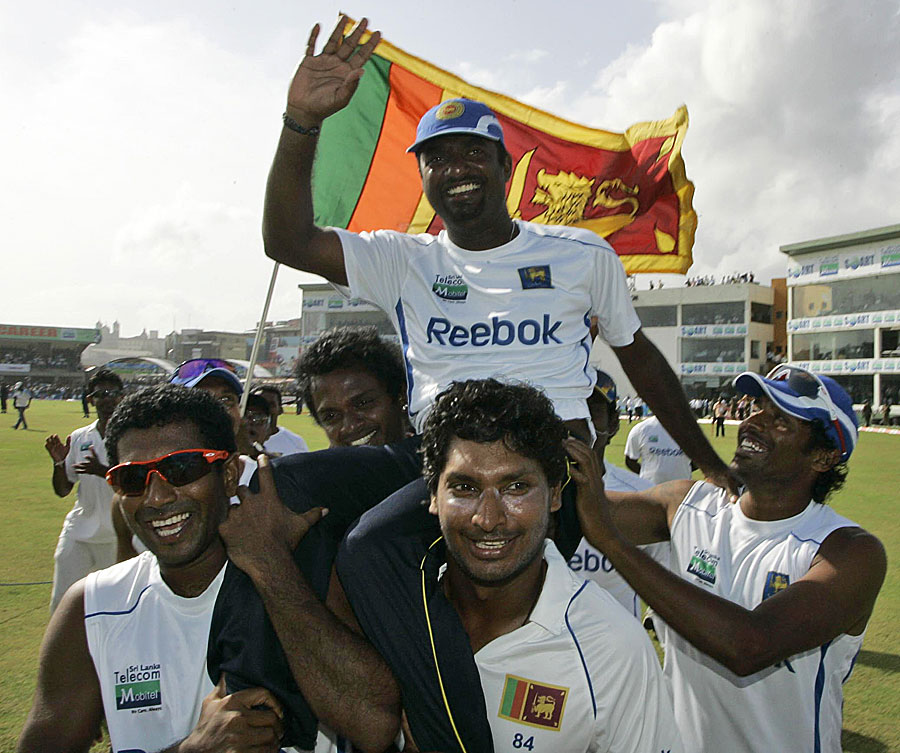 Muttiah Muralitharan is carried off the field by Kumar Sangakkara and Dammika Prasad