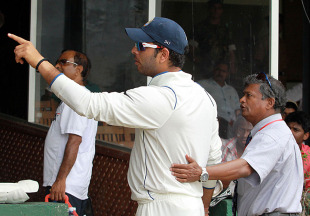 Yuvraj Singh gestures to the crowd as he's escorted by an official