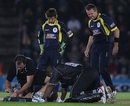 Dominic Cork grimaces as he notices the extent of Kieron Pollard's injury