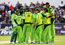 Mohammad Irfan towers over his team-mates as Pakistan gather at the fall of a wicket