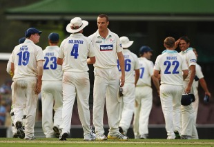 Stuart Clark and his team-mates gather after a wicket