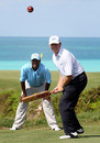Brian Lara looks on as golf star Ernie Els has a go at cricket ahead of the PGA Grand Slam of Golf