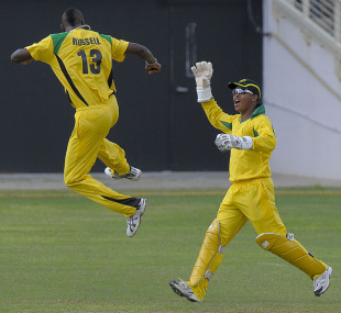 Andre Russell celebrates one of his six wickets with Carlton Baugh