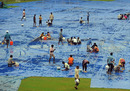 Groundstaff mop up the water on the covers at the Nehru Stadium in Margao, Margao, October 23, 2010