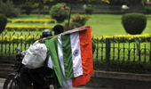 A man carries the Indian tri-colour flags on the back of a motorcycle