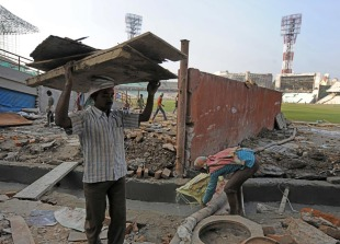Construction workers remove debris during the renovation of Eden Gardens, Kolkata, January 5, 2011