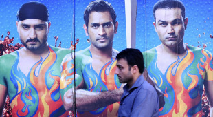 A commuter walks past an advertisement featuring photographs of Harbhajan Singh, MS Dhoni and Virender Sehwag, Mumbai, February 9, 2011