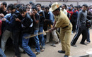 A policeman uses a bamboo stick to control the crowd queuing up for tickets for the India-England game outside the M Chinnaswamy stadium