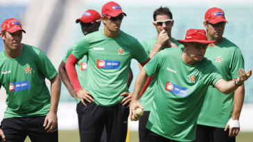 Zimbabwe players watch as coach Alan Butcher demonstrates a point