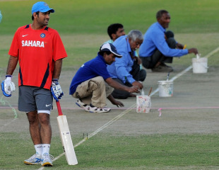 MS Dhoni bats during practice as the groundstaff prepares the pitch, Delhi, March 8, 2011