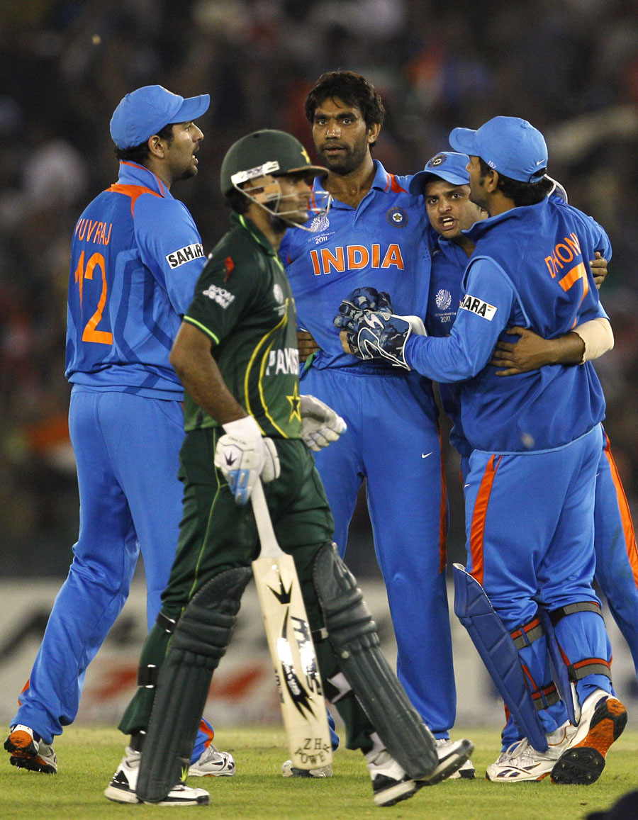 The Indian fielders mill around Munaf Patel after he dismissed Mohammad Hafeez