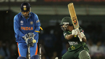 MS Dhoni watches as Asad Shafiq's middle stump is pegged back by Yuvraj Singh