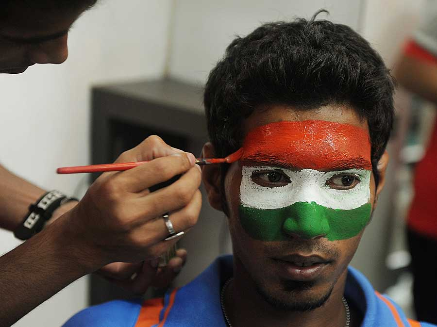 An Indian fan gets his face painted on the eve of the World Cup final