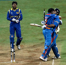 Kumar Sangakkara watches as MS Dhoni and Yuvraj Singh join in an embrace mid-pitch