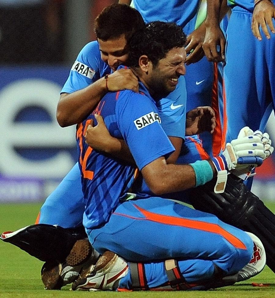 An emotional Yuvraj Singh is embraced by Suresh Raina
