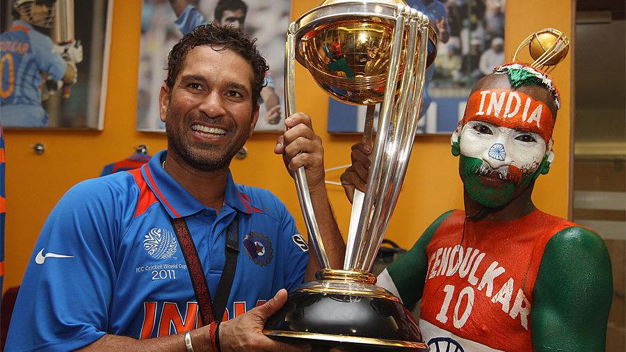 Sachin Tendulkar holds aloft the World Cup with one of his long-time fans, Sudhir Gautam