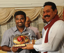 Muttiah Muralitharan is presented with a souvenir by Sri Lankan president Mahinda Rajapakse