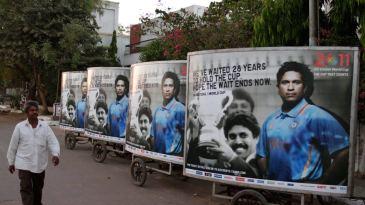 A man walks past a hoarding featuring Sachin Tendulkar and Kapil Dev
