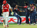 Varun Aaron celebrates with his team-mates after ending Adam Gilchrist's stay
