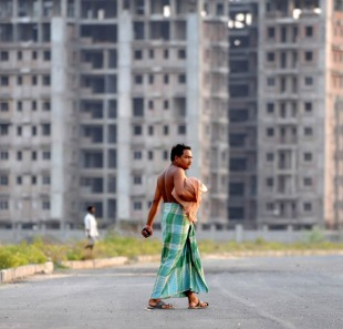 An Indian villager crosses a road passing new large-scale residential developments in Rajarhat, close to Kolkata
