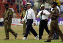 Rudi Koertzen and BC Cooray are escorted off the field by security officials after another wretched day for both of them, Sri Lanka v England 2nd Test, Kandy, March 10, 2001