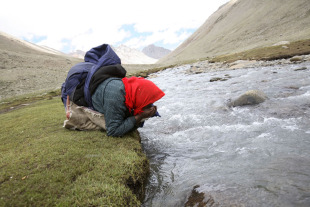 A Tibetan nomad drinks water from a river at Mount Kailash, June 16, 2007