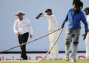 MS Dhoni points to umpire Ian Gould to some wet spots in the outfield after a rain interruption, West Indies v India, 2nd Test, Bridgetown, 5th day, July 2, 2011