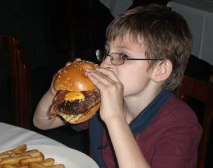 A boy eats a burger