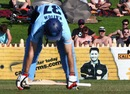 Simon Katich stretches in front of an advertising sign featuring Michael Clarke