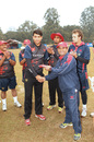 Debutant Babar Hayat receives his baggy red cap from Hong Kong Assistant Coach Jawaid Iqbal prior to the ACC Twenty20 Cup 2011 match against Nepal at the Tribhuvan University Ground in Kathmandu on 3rd December 2011