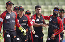 Yasir Arafat is congratulated by his team-mates on his three first-over scalps