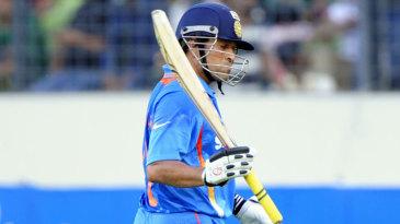 Sachin Tendulkar raises his bat as he walks off