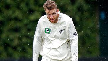 Daniel Vettori walks through the wind and rain