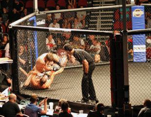 Adam Hollioake (bottom) in a mixed martial arts cage fight, Gold Coast, May 5, 2012