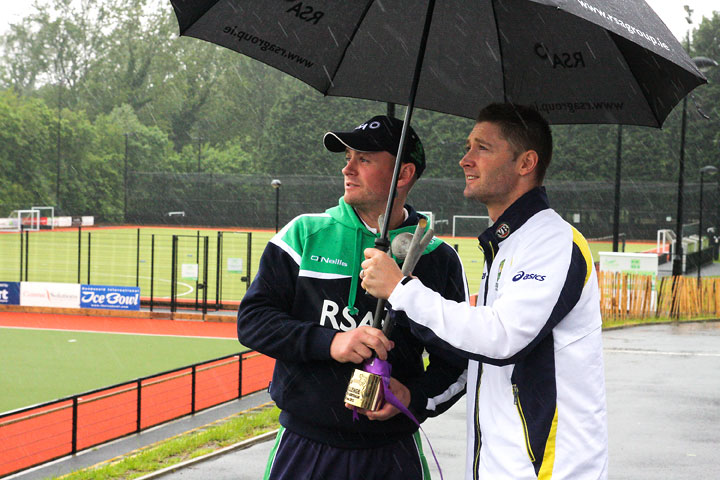 Michael Clarke and William Porterfield try to keep the RSA Challenge trophy dry