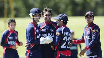 The Nepal team celebrates the fall of an Australian wicket