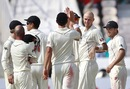 Chris Martin being congratulated by team-mates after picking up Virat Kohli